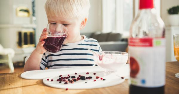 Lapsi juo puolukkamehua pöydän ääressä