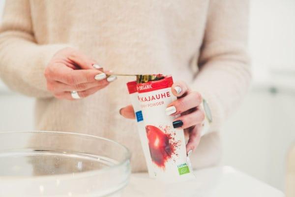 Nainen annostelee luomupuolukkajauhetta taikinaan