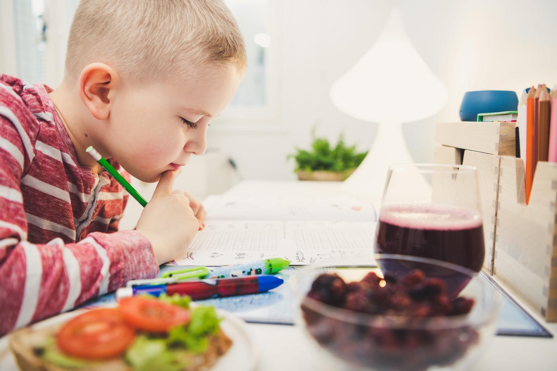 Poika tekee läksyjä ja syö välipalaa