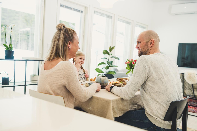 Perhe aamiaisella pöydän ääressä