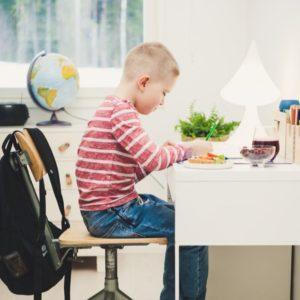 Poika tekee läksyjä pöydän ääressä